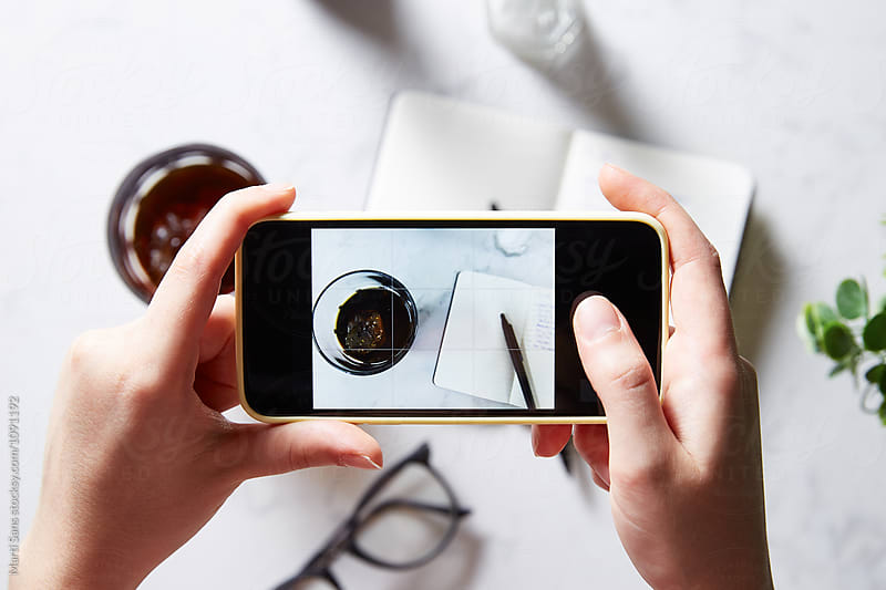 Person taking shot of notebook and glass of coffee using mobile phone by Martí Sans for Stocksy United