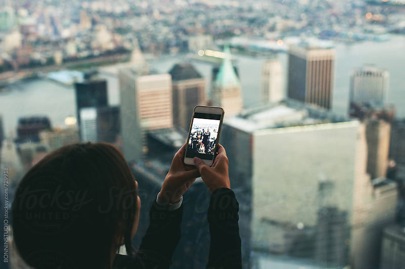 Woman taking a photo of the lower manhattan skyline. by BONNINSTUDIO for Stocksy United