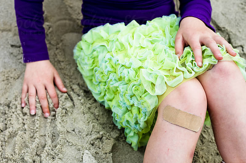 Little girl in a skirt with a band-aid on her knee by Carolyn Lagattuta for Stocksy United