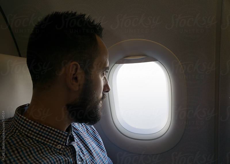 Young man looking out of the window on an airplane by ACALU Studio for Stocksy United