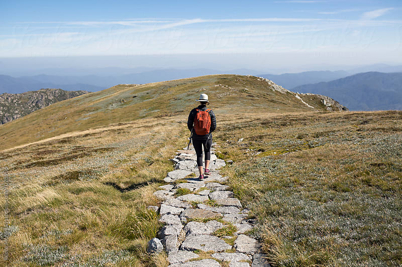 A female hiker walking away down a path by Reece McMillan for Stocksy United