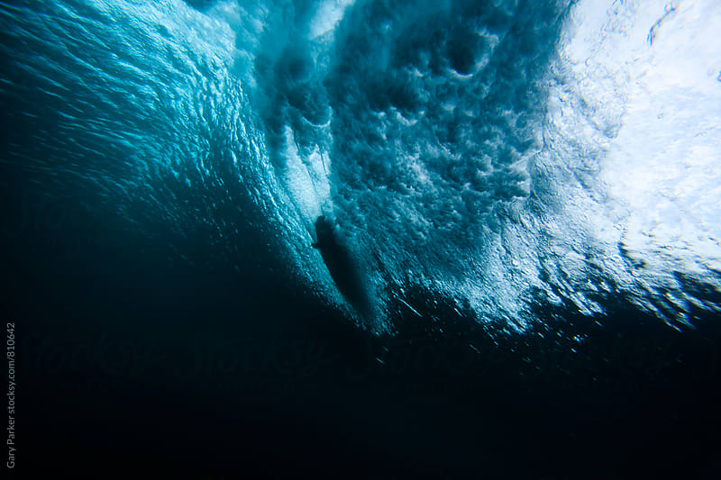 A surfboard slices through a breaking wave shot from below sea level by Gary Parker for Stocksy United