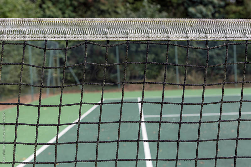 Close shot of a tennis net with lines and court behind by Paul Phillips for Stocksy United