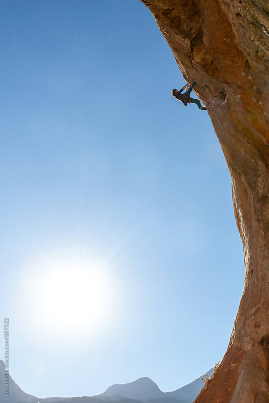 Young man rock climbing an overhanging wall by RG&B Images for Stocksy United