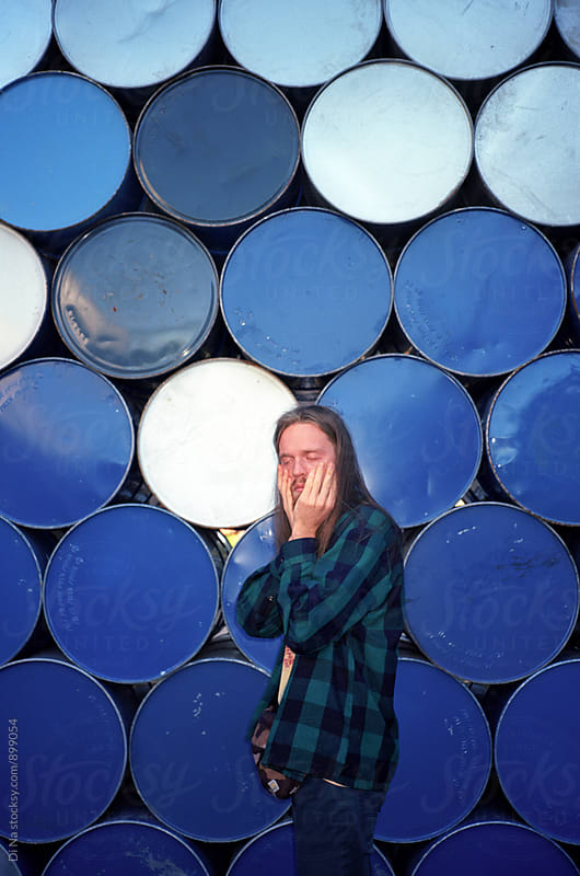 Young man covers his face against the background of blue barrels by Dina Lun for Stocksy United