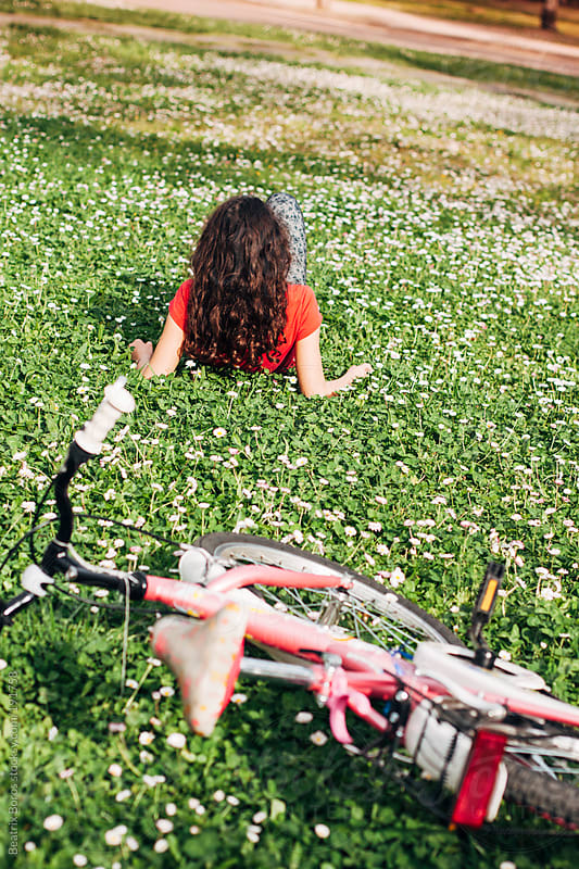Girl lying on the grass, her bycicle is behind her by Beatrix Boros for Stocksy United