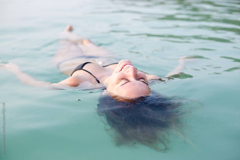 Beautiful young woman floating in the sea relaxing by Jovo Jovanovic for Stocksy United