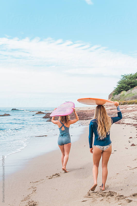 Two Women Walking on the Beach Carrying Surfboards on their Heads by Briana Morrison for Stocksy United