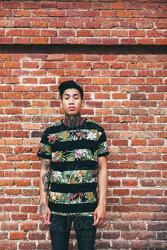 Portrait of a young tattooed man standing in front of a brick wall. by BONNINSTUDIO for Stocksy United