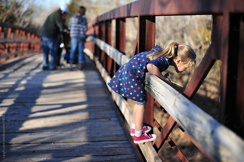 Young Girl Looks Over a Bridge with People in Background by Leigh Love for Stocksy United