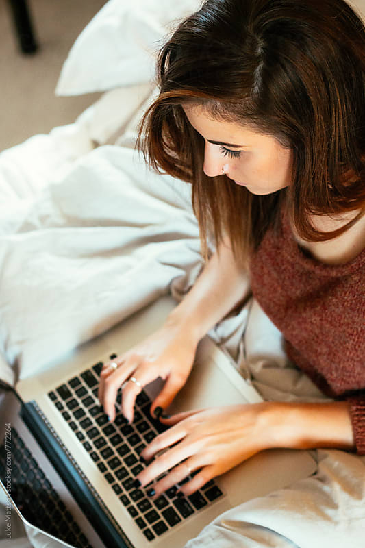 Young Brunette Woman Typing On Laptop In Bed by Luke Mattson for Stocksy United
