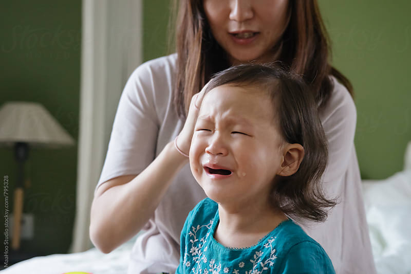 Toddler girl crying while her mother braiding her hair by Maa Hoo for Stocksy United