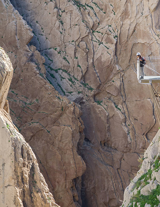 Woman looking down at the edge of a cliff in Caminito del Rey by ACALU Studio for Stocksy United