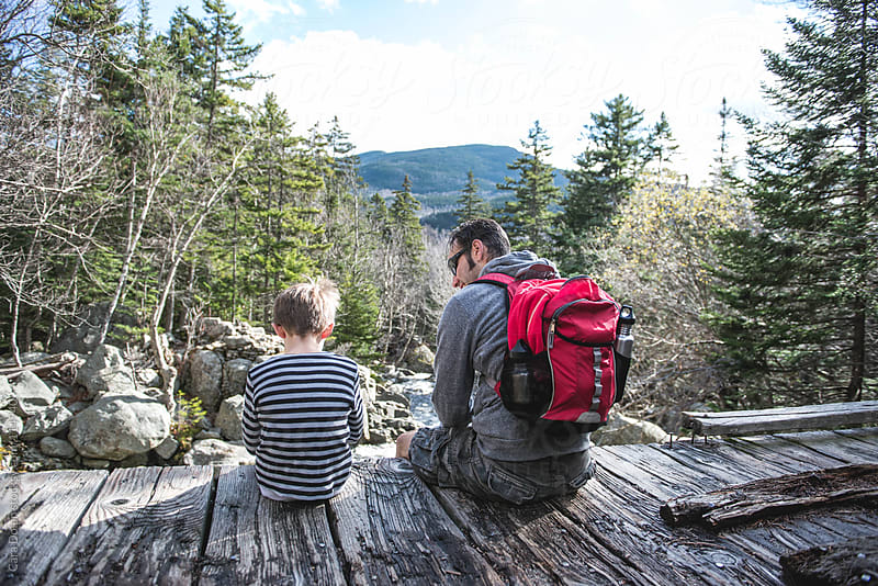 Boy and his dad rest together on a wooden bridge while hiking in the mountains by Cara Dolan for Stocksy United