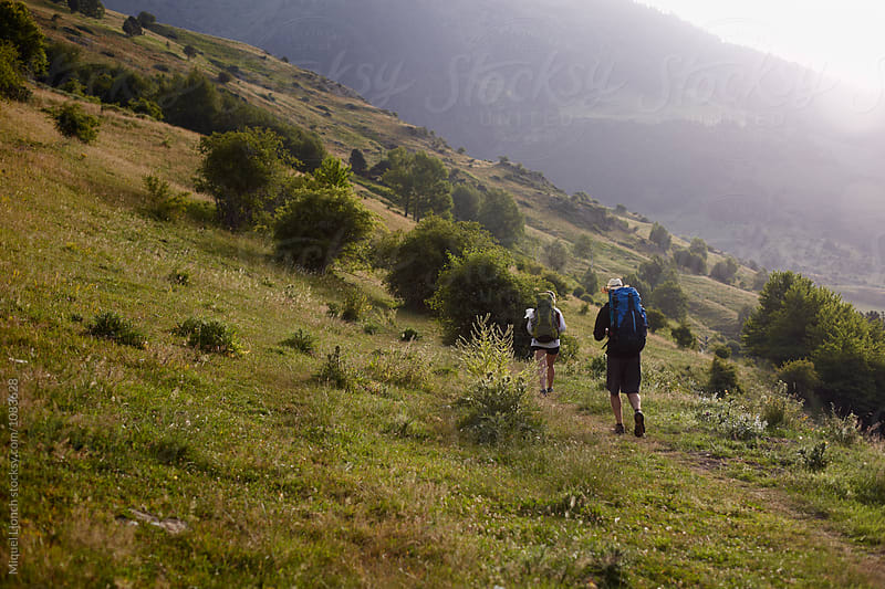 Backpackers in the morning going up the valley by Miquel Llonch for Stocksy United