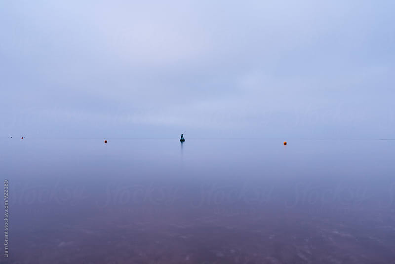 Cloudy sky a bouys reflected in a calm ocean at twilight. Norfolk, UK. by Liam Grant for Stocksy United