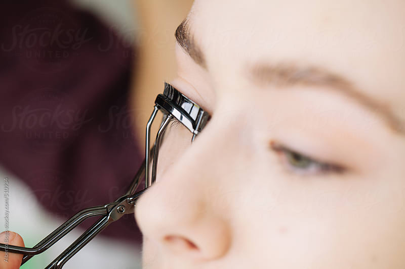 Makeup artist applying eyelash curler by Alberto Bogo for Stocksy United