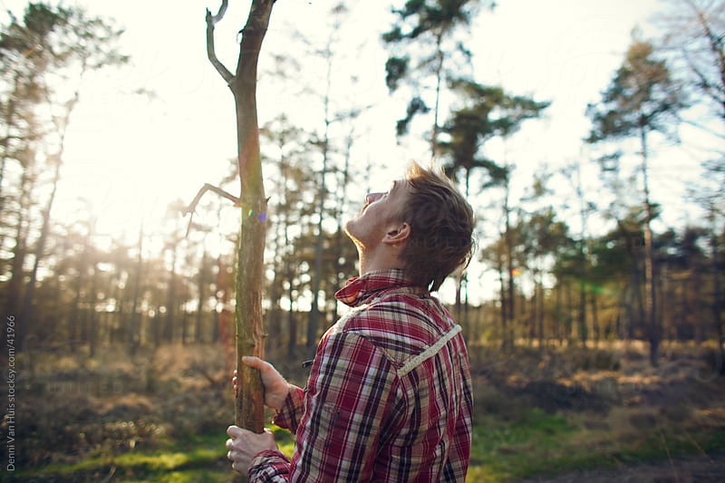 Young man collecting firewood in a forest  by Denni Van Huis for Stocksy United