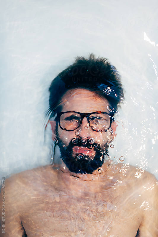 Man holding breath underwater in the bathtub. by BONNINSTUDIO for Stocksy United