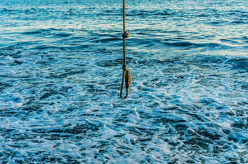 Rope swing over the waves by Richard Brown for Stocksy United