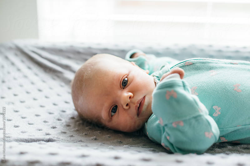 Newborn Baby Girl In Green Onesie Lying On Changing Table Looking At Camera by Luke Mattson for Stocksy United