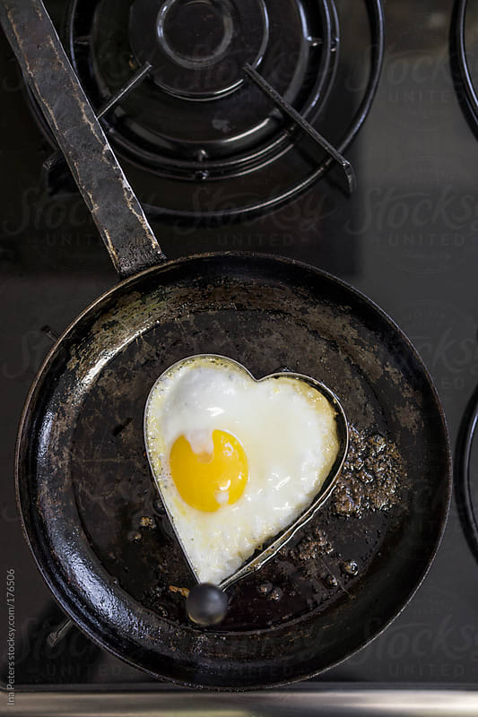 Food: Fried Heart-Shaped Egg in a Pan by Ina Peters for Stocksy United