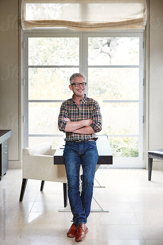 Portrait of mature man with grey hair working in home office by Trinette Reed for Stocksy United