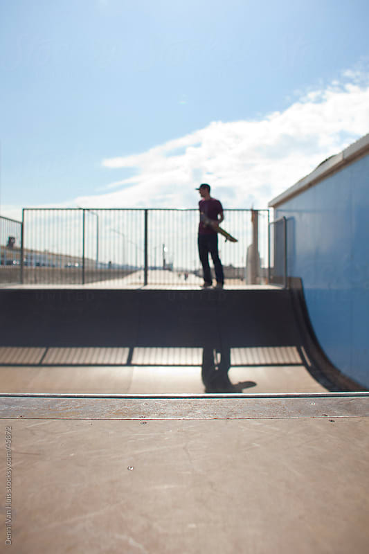 Young man holding his skateboard and stands on a skate ramp by Denni Van Huis for Stocksy United