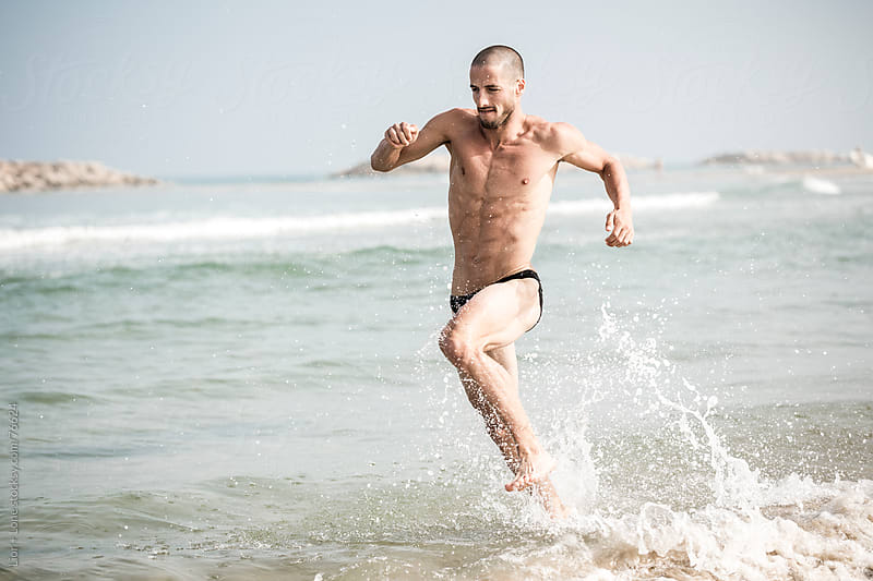 Man running training for triathlon at the beach by Lior + Lone for Stocksy United