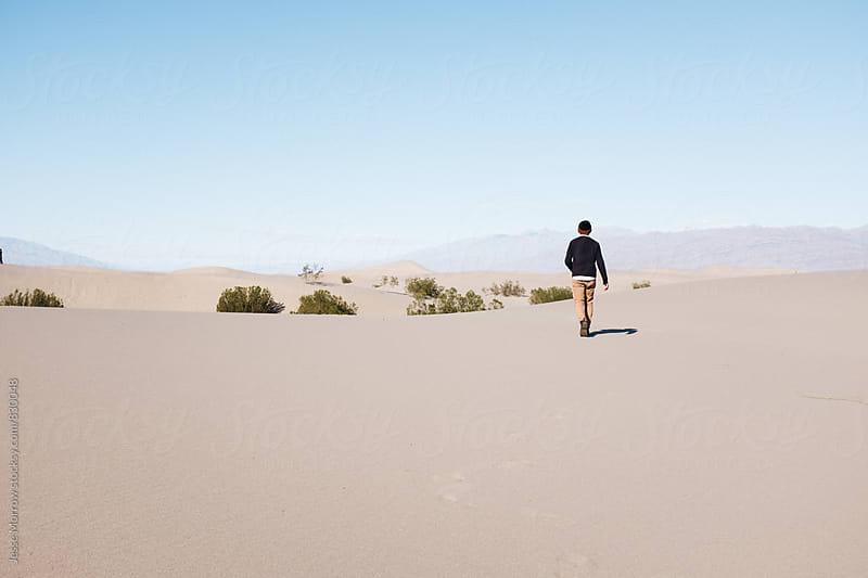 male walks through desert sand dunes by Jesse Morrow for Stocksy United