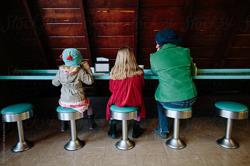 mom and daughters at donut shop by Brian Powell for Stocksy United