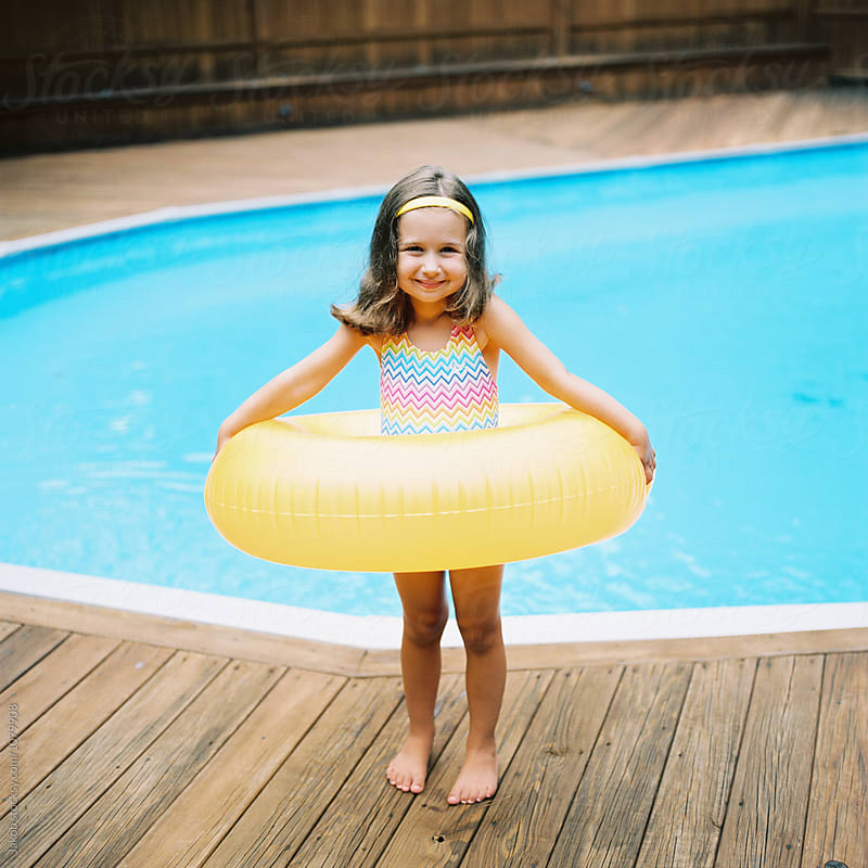 Cute young girl with a big inner tube standing by a swimming pool by Jakob for Stocksy United