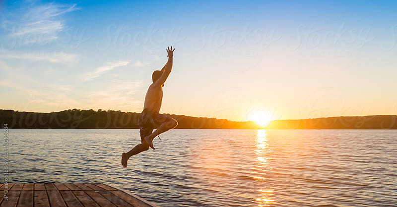 Man Jumping Into Warm Summer Cottage Lake At Sunset from Dock by JP Danko for Stocksy United