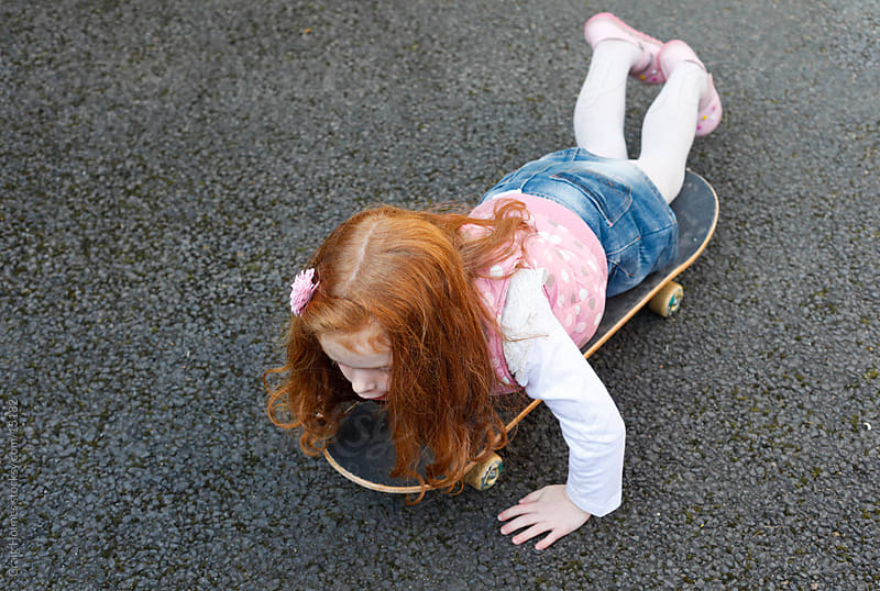 6 year old girl with red hair on a skateboard by Craig Holmes for Stocksy United