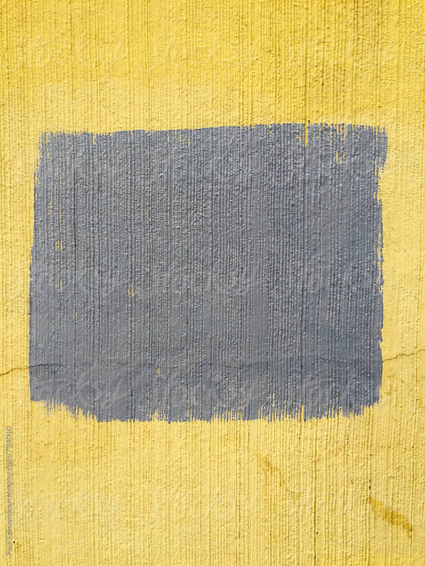 Yellow and grey paint covering graffiti tags on urban wall, close up by Paul Edmondson for Stocksy United
