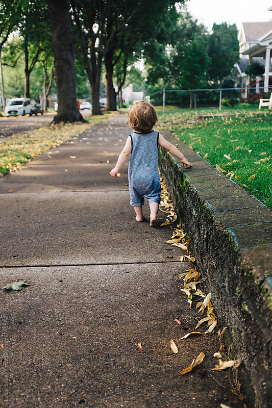 A young toddler walking on a sidewalk after a summer storm. by Lucas Saugen for Stocksy United