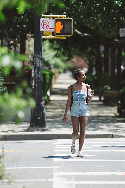 Young woman crossing street in her neighborhood by Lauren Naefe for Stocksy United