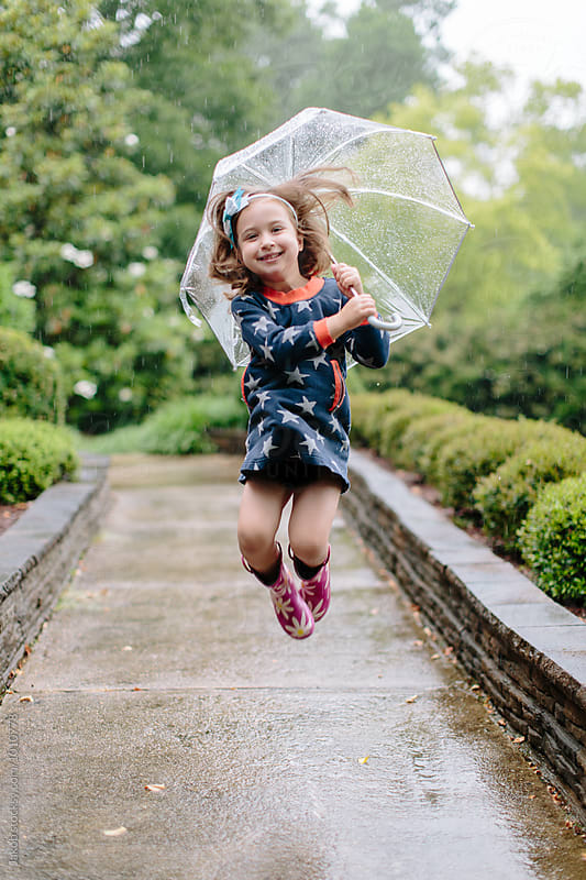 Cute young girl jumping in the rain with an umbrella by Jakob for Stocksy United