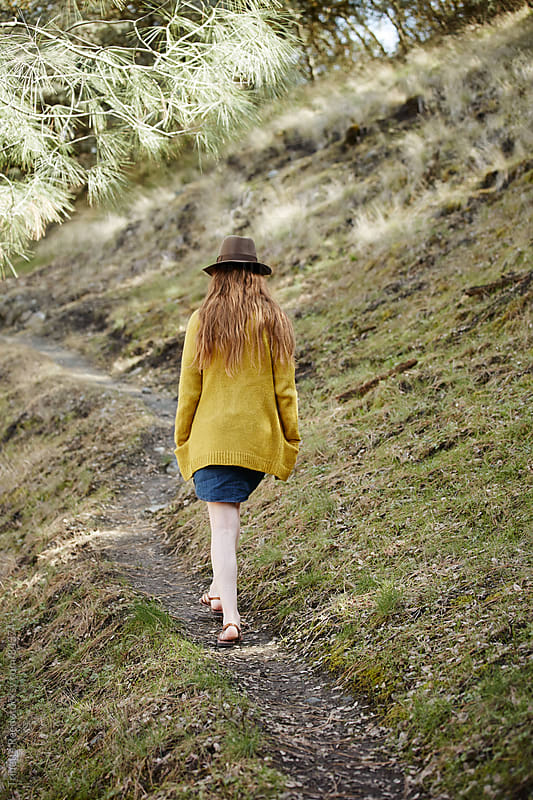 Redhead woman walking on narrow trail by Trinette Reed for Stocksy United