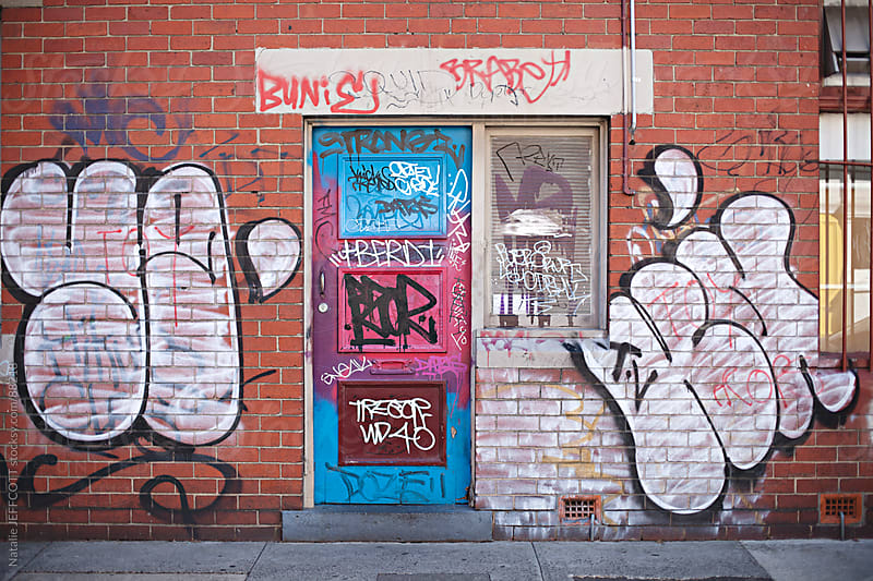 inner city building covered in graffiti tags by Natalie JEFFCOTT for Stocksy United