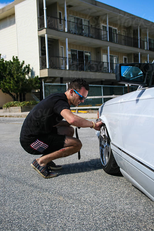 Hip young man cleans the front wheels of his white car by Peyton Weikert for Stocksy United