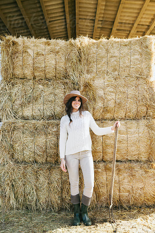 Woman farmer with hoe standing on a haystack. by BONNINSTUDIO for Stocksy United