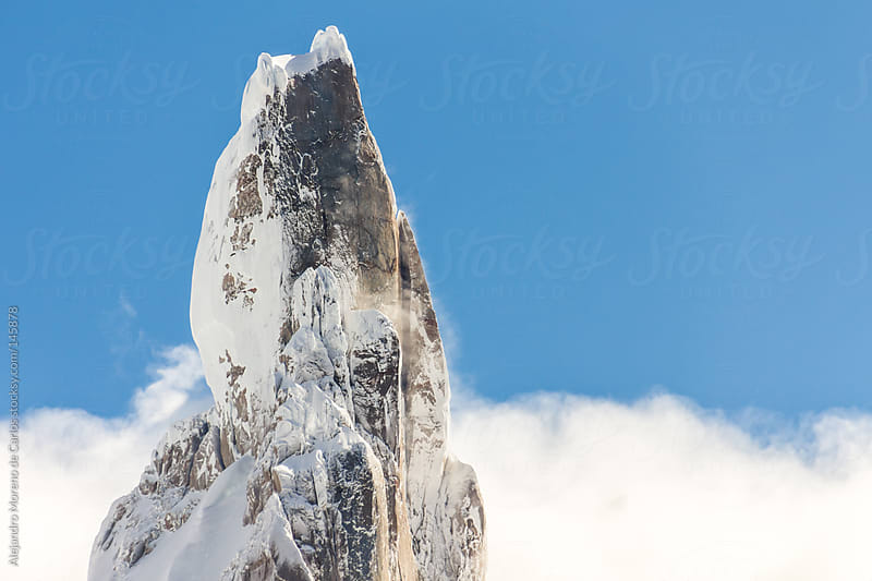 Mountain peak with snow over the clouds and blue sky. Cerro Torre, El Chalten, Patagonia by Alejandro Moreno de Carlos for Stocksy United