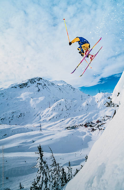 Skier jumping off snow cornice in winter mountain landscape by Soren Egeberg for Stocksy United
