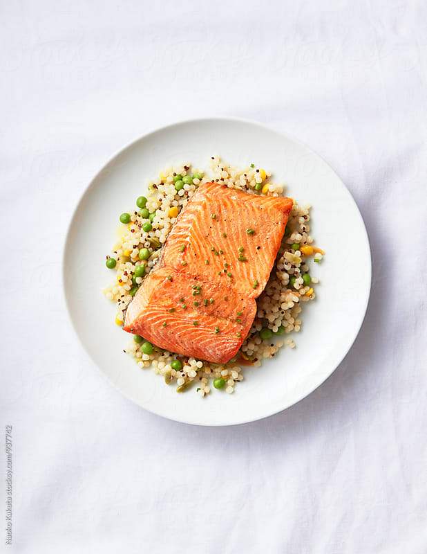 bakes salmon over cooked couscous and peas on white plate on white linen table cloths by Naoko Kakuta for Stocksy United