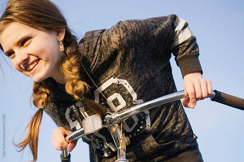A young teen girl leans on her handle bars and smiles. by Tana Teel for Stocksy United
