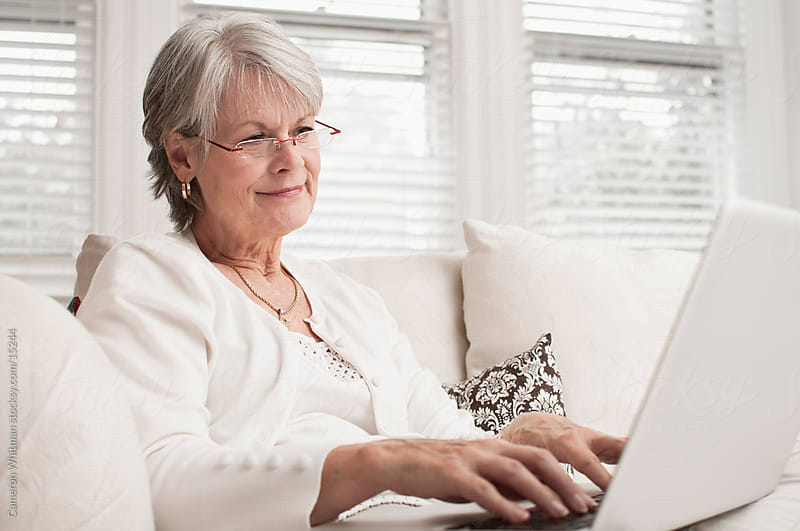 Mature woman surfing the internet by Cameron Whitman for Stocksy United