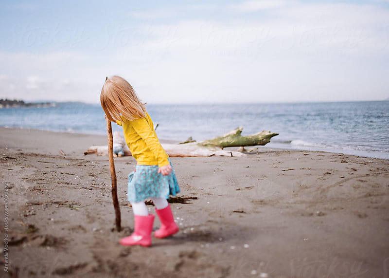 Little girl Walking on the Beach with a Walking Stick by Amanda Voelker for Stocksy United