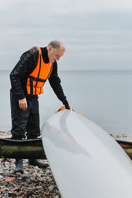 Senior man cleaning kayak by Lior + Lone for Stocksy United