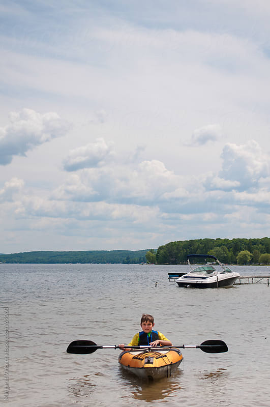 young boy floats on a lake in a kayak by Margaret Vincent for Stocksy United